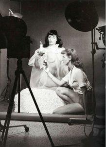 Bunny Yeager réglant la lumière pour une photo avec Bettie Page.