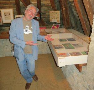 Jean-Luc Fornelli devant la vitrine où sont exposés ses collages.